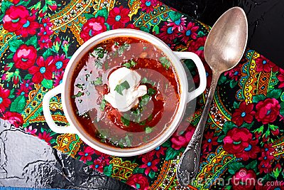 Ukrainian traditional borsch. Russian vegetarian red soup in white bowl on black background. Top view. Borscht, borshch with bee