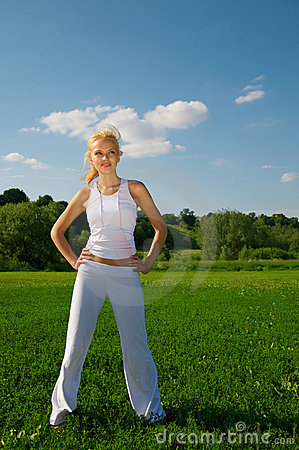 Young woman standing on a green grass