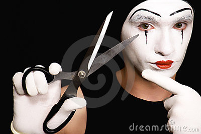 Mime with scissors on  black background