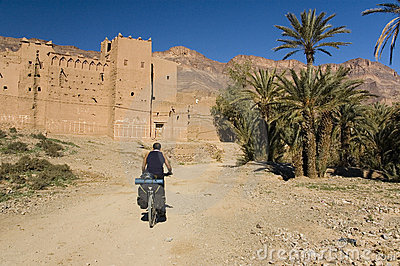 Man cycling near a small village in south Morocco
