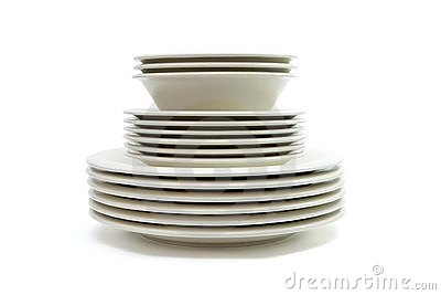 Stack of beige dinner plates, soup plates and sauc