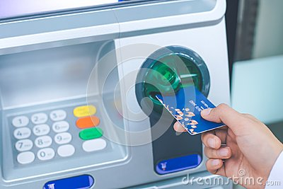 Woman`s hand inserting debit card into an ATM