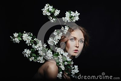 Art beauty portrait of nude woman on black background. Branches
