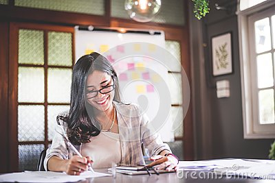 Business beautiful Asian woman working and writing note