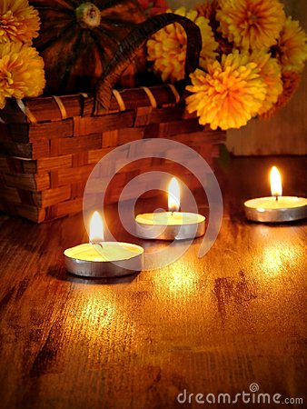 Lighted candles and a wicker basket with a pumpkin and flowers in the background
