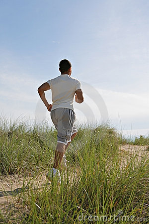 Young Man Jogging in the Sandy Beach Area