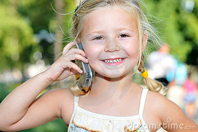 Beautiful little girl talks by a mobile phone