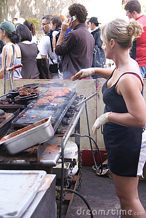 Young blonde woman working a hot grill