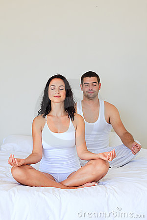 Couple meditating in bed