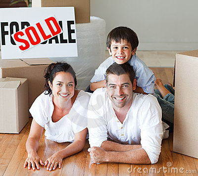 Smiling family on the floor after buying house