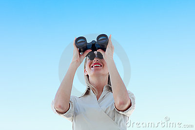 Businesswoman looking through binoculars outdoors