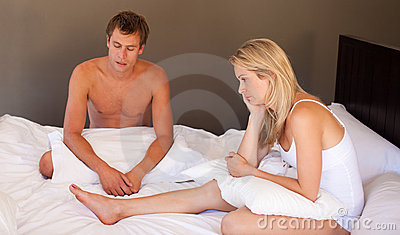 Couple sitting on bed in silence