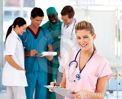 Blonde nurse with her team in the background