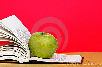 Green apple and open book