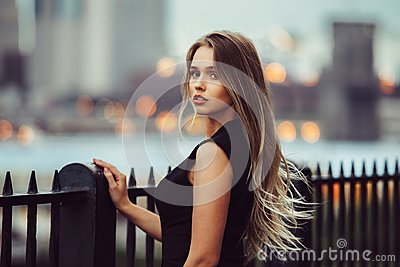 Gorgeous young model woman with perfect blonde hair looking at camera posing in the city wearing black evening dress
