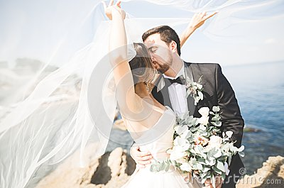 Wedding couple, groom, bride with bouquet posing near sea and blue sky