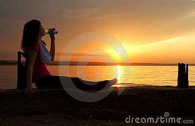 Beautiful young woman drinking water - sunset.