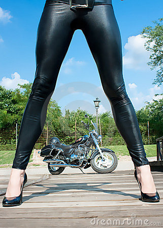 Long  woman`s  legs  with view on motorbike