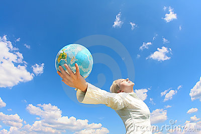 Woman holding a globe under sky