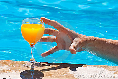 Man's hand and glass with orange juice