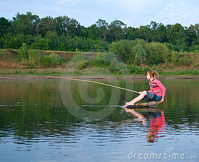 Girl-fisher sits on a log in the middle