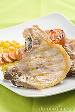Tasty pork chop with corn carrot tomato