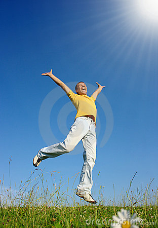 Young man jumping on the meadow