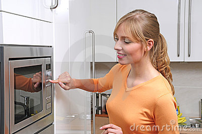 Blond woman with a microwave
