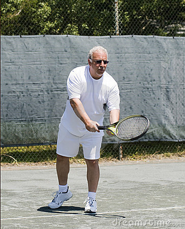 Middle age tennis player service motion on court