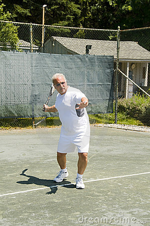 Middle age tennis player forehand on court