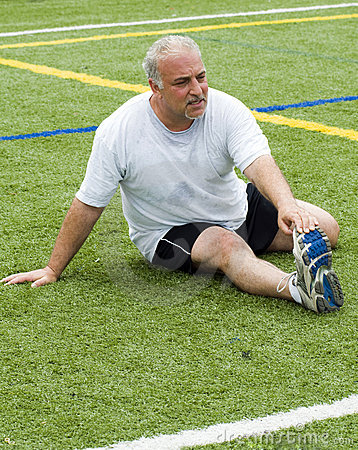 Middle age man stretching on sports field