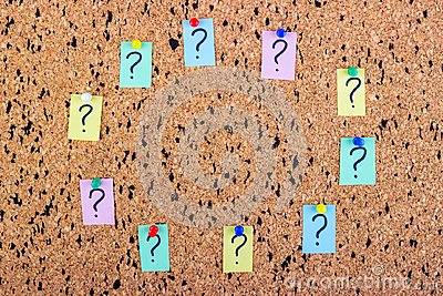 uncertainty or doubt concept, question mark on a sticky note on cork bulletin board