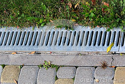 Metal grate of rainwater drainage system in a park