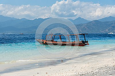 Small wooden boat on blue beach with cloudy sky and Lombok island on background. Gili Trawangan, Indonesia