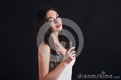 Young woman vaping e-cigarette on black