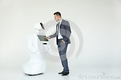 A stylish businessman communicates with a robot. Cybernetic system today. Modern Robotic Technologies. Humanoid