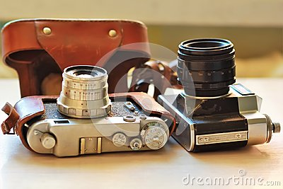 Two old school vintage photo cameras on light brown table. One in brown retro leather case holder