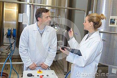 Two workers in labcoat working at factory