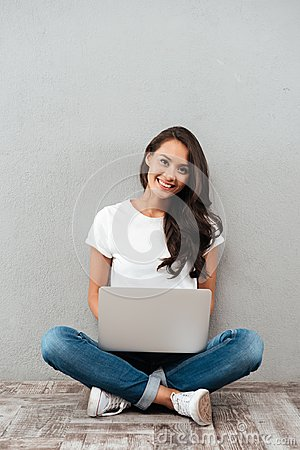 Happy young asian woman working on laptop computer