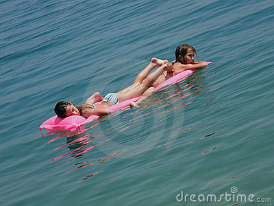 Girl lying on mattres in blue sea