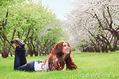 Young girl lying on green grass