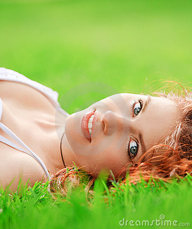Young pretty girl lying on grass