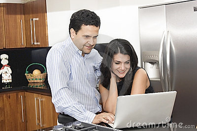 Happy couple working in kitchen