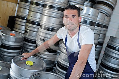 Worker with beer barrels at brewery
