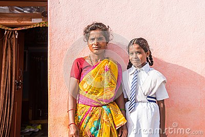 PUTTAPARTHI, ANDHRA PRADESH, INDIA - JULY 9, 2017: Indian woman in sari and girl in school uniform. Copy space for text. Close-up.