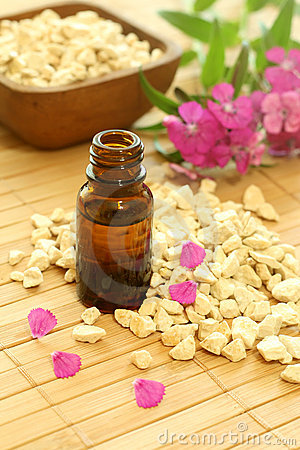 Bottle of essence oil with flowers and stones