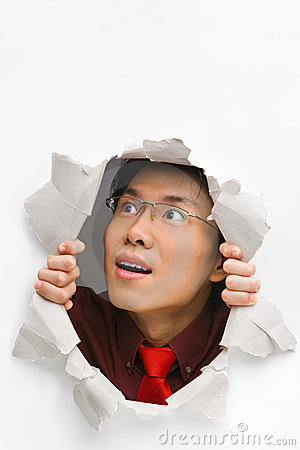 Man looking up happily from hole in wall
