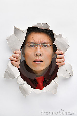 Man gazing seriously from hole in wall