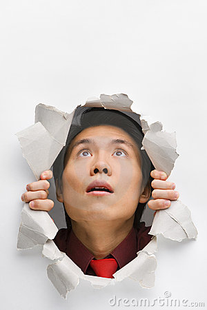 Man looking up surprisingly from hole in wall