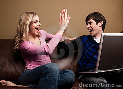 Couple celebrating with a computer